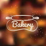 Bakery cafe hand drawn logo with rolling pin stretching the dough on blurred background. Royalty Free Stock Images