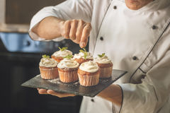 Bakery chef cooking bake in the kitchen professional. Decorating Royalty Free Stock Images