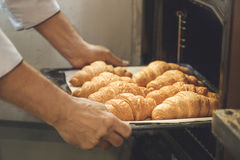 Bakery chef cooking bake in the kitchen professional. Holding croissants Stock Photo