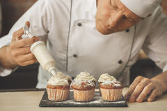 Bakery chef cooking bake in the kitchen professional. Put cream Stock Image