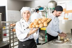 Bakery Chef With Delicious Bread Items In Tray. Confident head pastry chef carrying baked chouxs at kitchen counter stock photo