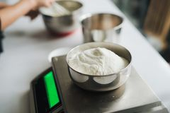 Bakery chef weighing flour on the digital scale stock photography