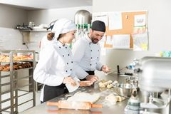 Pastry Chefs Preparing Dough In Bakery. Bakery colleagues preparing dough for pastries in kitchen stock photos