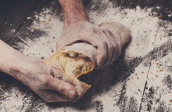 Bakery concept background. Hands breaking bread loaf Stock Photography