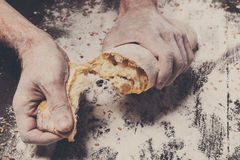 Bakery concept background. Hands breaking bread loaf Royalty Free Stock Photo