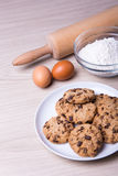 Bakery concept - chocolate chip cookies, eggs and flour on woode Stock Photos
