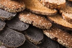 Bakery concept. Plenty of sliced bread background. Sliced black bread gradient background. Bakery and grocery concept. Fresh, healthy whole grain sliced sorts of Stock Photography