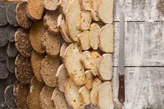 Bakery concept. Plenty of sliced bread background. Sliced sorts of bread gradient background. Bakery and grocery concept with knife. Black, rye and white loaves stock photos