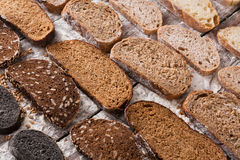 Bakery concept. Plenty of sliced bread background. Sliced sorts of bread gradient background. Bakery and grocery concept. Fresh, healthy whole grain sliced sorts stock photos