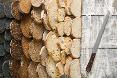 Bakery concept. Plenty of sliced bread background. Sliced sorts of bread gradient background. Bakery and grocery concept with knife. Black, rye and white loaves stock image