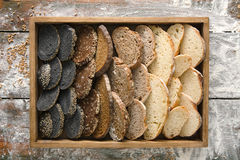 Bakery concept. Plenty of sliced bread background. Sliced sorts of bread gradient background on wood. Bakery and grocery concept. Black, rye and white loaves royalty free stock image