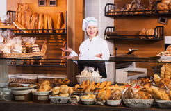 Bakery employee offering bread. Aged bakery employee offering bread and different pastry for sale Royalty Free Stock Photos