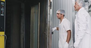 Bakery engineer and his assistance in a white uniform load the bread on the oven machine , engineer monitors all the. Process assistant programs the temperature stock video