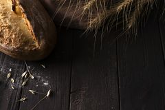 Bakery - gold rustic crusty loaves of bread and buns on black background. royalty free stock image