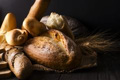 Bakery - gold rustic crusty loaves of bread and buns on black background. Stock Image