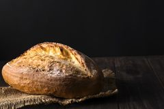 Bakery - gold rustic crusty loaves of bread and buns on black background. royalty free stock photo