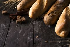 Bakery - gold rustic crusty loaves of bread and buns on black chalkboard background. royalty free stock photos