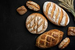 Bakery - gold rustic crusty loaves of bread and buns on black chalkboard background. royalty free stock image