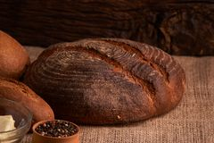Bakery - gold rustic crusty loaves of bread and buns on black chalkboard background. Still life captured from above. Bakery - gold rustic crusty loaves of bread royalty free stock photography