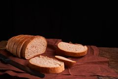 Bakery - gold rustic crusty loaves of bread and buns on black chalkboard background. Still life captured from above. Bakery - gold rustic crusty loaves of bread royalty free stock image