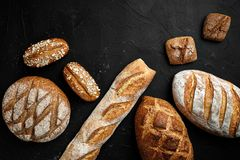 Bakery - gold rustic crusty loaves of bread and buns on black chalkboard background. stock photography