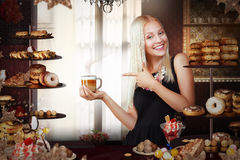 Bakery. Happy Saleswoman with Cup of Coffee in Bakeshop Stock Photo
