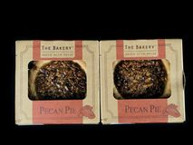 The Bakery Individual Size Pecan Pies. On a black backdrop stock photo