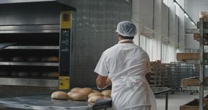 Bakery industry workers unloaded the cooked bread from the oven machine then load the bread in the special shelves. 4k stock video