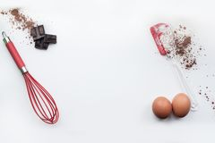 Bakery ingredients - flour, eggs, cocoa, chocolate on white table. Sweet pastry baking concept. Flat lay, copy space, top view.  Stock Images