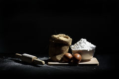 Bakery ingredients, flour, eggs and wooden rolling pin Stock Image