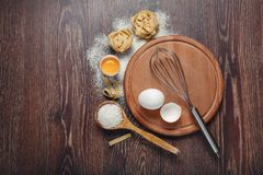 Bakery ingredients. Flour with raw eggs for dough pasta on a wooden background stock photos
