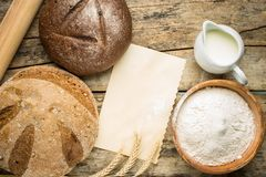 Bakery ingredients with fresh loaf of bread. Stock Image