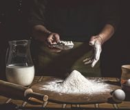 Bakery. Man preparing bread, Easter cake, Easter bread or cross-buns on wooden table in a bakery close up. Man preparing bread dou. Bakery. Man preparing bread Royalty Free Stock Photography