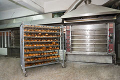 Bakery oven. Wired rack filled with fresh baked bread by the bakery oven Stock Images