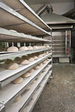 Bakery oven. Wired rack filled with fresh uncooked bread prepared for stacking into the bakery oven Royalty Free Stock Image