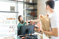 Bakery Owner Receiving Cashless Payment From Man. Smiling saleswoman receiving credit card payment from male customer in bakery royalty free stock image