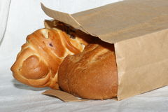 Bakery in paper bag. Yummy  brown bakery in beige craft paper bag on white tablecloth Royalty Free Stock Image