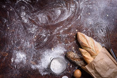 Bakery produce and ingredients: flour, eggs on dark background. Rustic bread roll or french baguette. Top view, copy space. Royalty Free Stock Photo