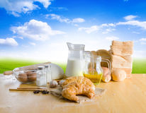 Bakery product and ingredients on wooden table over green field Stock Images