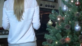 Bakery production. Woman placing the baking dish into the oven stock video footage