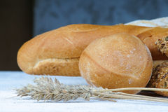 Bakery products and wheat ears on a table Stock Photos