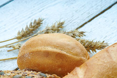 Bakery products and wheat ears on a table Stock Photography