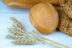 Bakery products and wheat ears on a wooden table Royalty Free Stock Photos