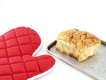 Red oven glove with bread isolated on white background Royalty Free Stock Image