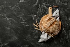 Bakery - round loaf of rustic bread on black background. Gold round loaf of rustic bread and ears of wheat on wooden board captured from above top view, flat lay stock images
