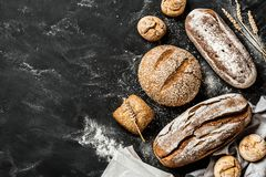 Bakery - rustic crusty loaves of bread and buns on black Stock Images