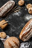 Bakery - rustic crusty loaves of bread and buns on black. Bakery - gold rustic crusty loaves of bread and buns on black chalkboard background. Still life royalty free stock photography