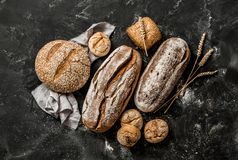 Bakery - rustic crusty loaves of bread and buns on black. Bakery - gold rustic crusty loaves of bread and buns on black chalkboard background. Still life royalty free stock image