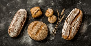 Bakery - rustic crusty loaves of bread and buns on black Royalty Free Stock Photo