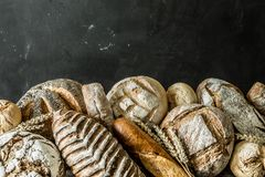 Bakery - rustic crusty loaves of bread and buns on black. Bakery stall - gold rustic crusty loaves of bread and buns exposed on black chalkboard background stock photos